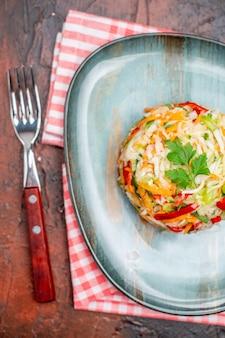 Vue de dessus de la salade de légumes en forme de plaque intérieure ronde sur la table sombre