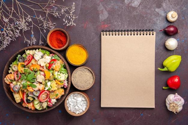 Vue de dessus de la salade de légumes frais avec assaisonnements sur fond noir