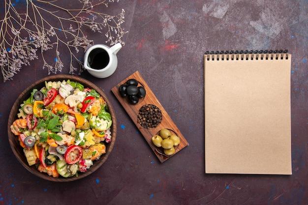 Vue de dessus de la salade de légumes frais aux olives sur fond noir