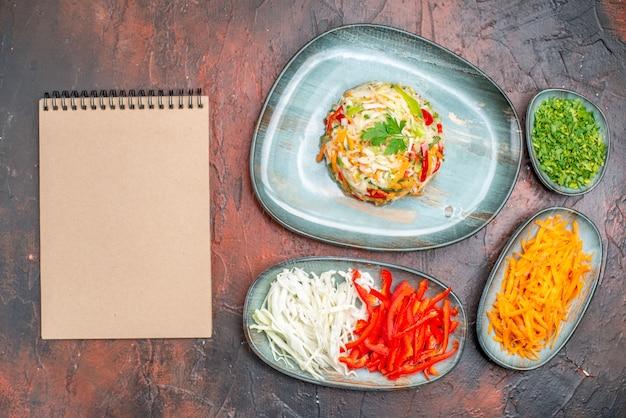 Vue de dessus de la salade de légumes frais avec du chou carotte et des poivrons tranchés sur la table sombre