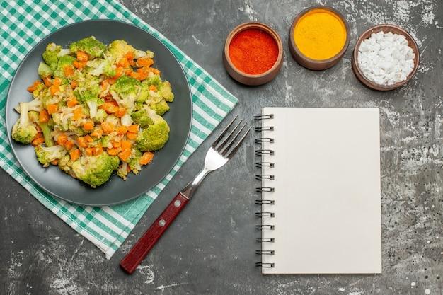 Vue de dessus de la salade de légumes frais et sains, serviette dépouillée verte et ordinateur portable sur table grise