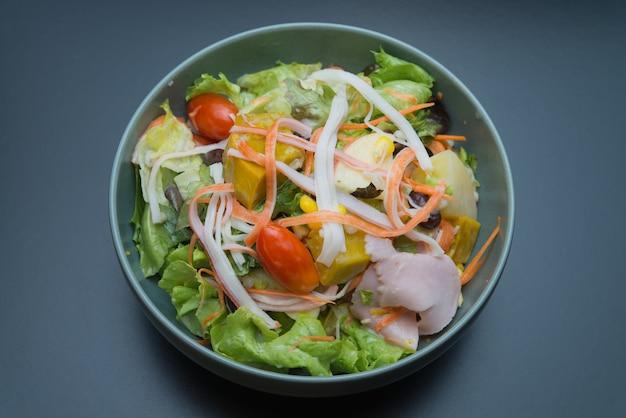 Vue de dessus de la salade de légumes avec jambon, bâtonnet de crabe, pomme et maïs sucré.
