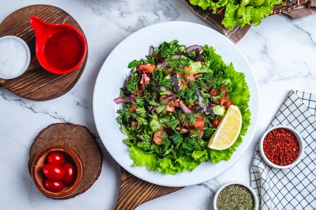 Vue de dessus salade de légumes avec des légumes verts sur la laitue dans une assiette avec une tranche de citron et de tomates cerises
