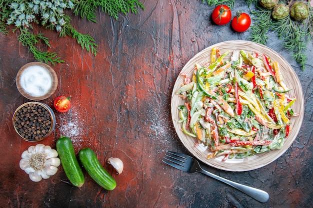 Vue de dessus salade de légumes sur plaque fourche tomates branches de pin concombres ail sur table rouge foncé copy place