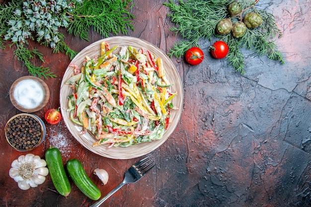 Vue de dessus salade de légumes sur plaque fourche tomates branches de pin concombres ail sur table rouge foncé place libre