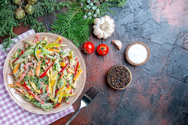Vue de dessus salade de légumes sur plaque nappe sel fourchette et poivre noir tomates ail sur table rouge foncé