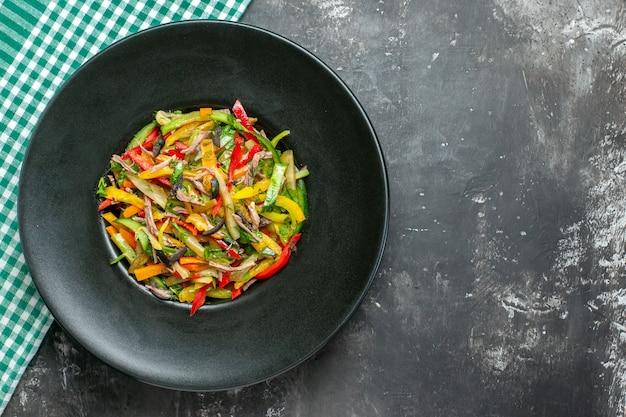 Vue de dessus de la salade de légumes savoureuse sur une surface sombre