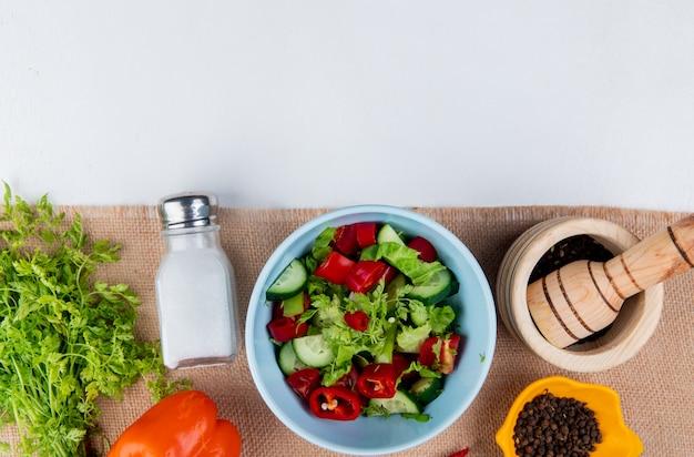 Vue de dessus de la salade de légumes avec un tas de graines de poivre de coriandre poivre noir sur un sac et une surface blanche avec copie espace