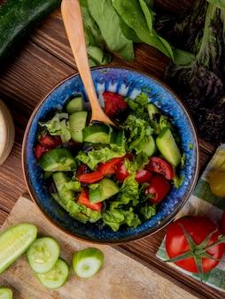 Vue de dessus de salade de légumes avec tomates basilic épinards concombres coupés et tranchés sur la surface en bois