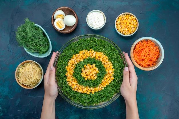 Vue de dessus salade de légumes verts à l'intérieur d'une plaque de verre ronde avec des œufs et des carottes en tranches sur le bureau bleu foncé.