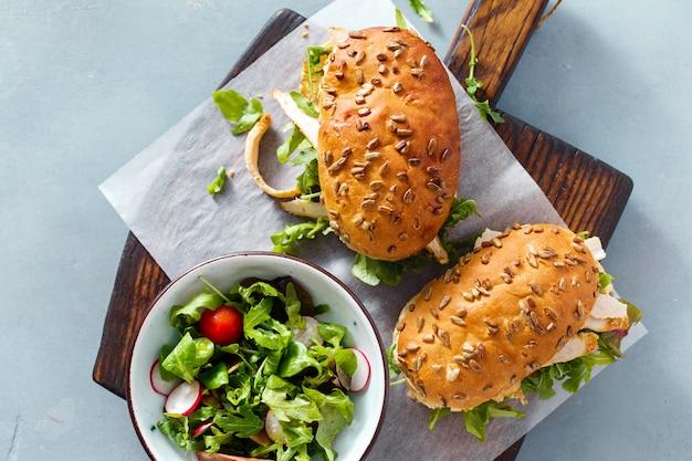 Vue de dessus de salade de planche de bois de sandwichs au poulet roquette