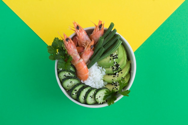 Vue de dessus sur la salade de poke aux crevettes rouges et légumes verts dans le bol blanc sur fond coloré. espace de copie.