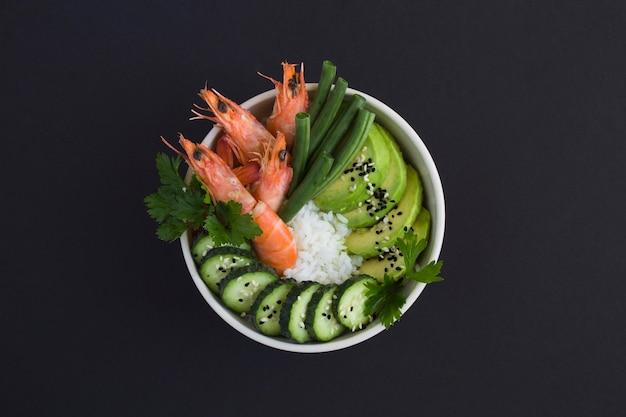 Vue de dessus sur la salade de poke aux crevettes rouges et légumes verts dans le bol blanc sur fond noir. fermer.