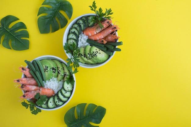 Vue de dessus sur la salade de poke aux crevettes rouges et légumes verts dans les bols blancs sur fond tropical. espace de copie.