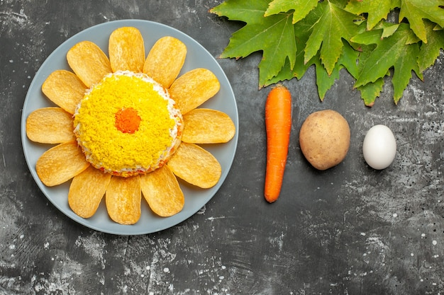 Vue de dessus de la salade avec pomme de terre carotte et oeuf et feuilles sur fond sombre