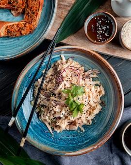 Vue de dessus de la salade avec poulet au chou haché et graines noires dans une assiette avec des baguettes sur bois