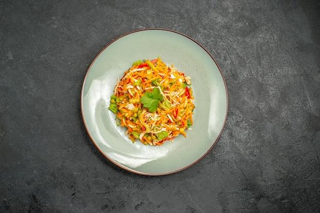 Vue de dessus de la salade de poulet aux légumes à l'intérieur de la plaque sur la nourriture diététique de la salade de santé sombre