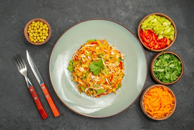 Vue de dessus de la salade de poulet aux légumes à l'intérieur de la plaque sur une salade de santé diététique grise