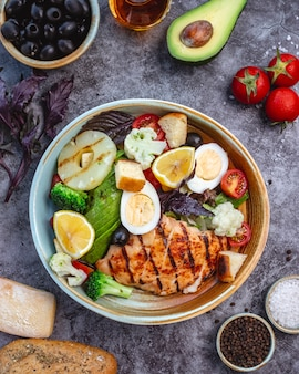 Vue de dessus de la salade de régime sain avec du poulet grillé brocoli chou-fleur tomate laitue avocat et laitue