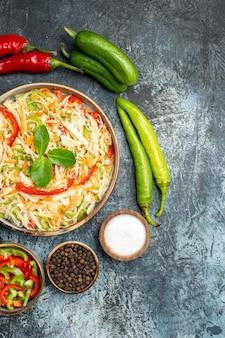 Vue de dessus de la salade savoureuse avec des légumes frais sur une surface sombre