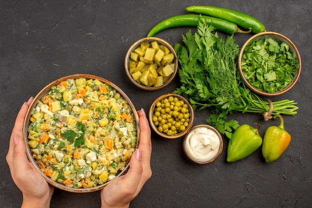Vue de dessus salade savoureuse avec des verts sur fond sombre