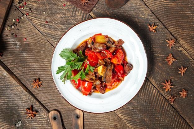 Vue de dessus sur salade tiède avec boeuf aubergine et tomates
