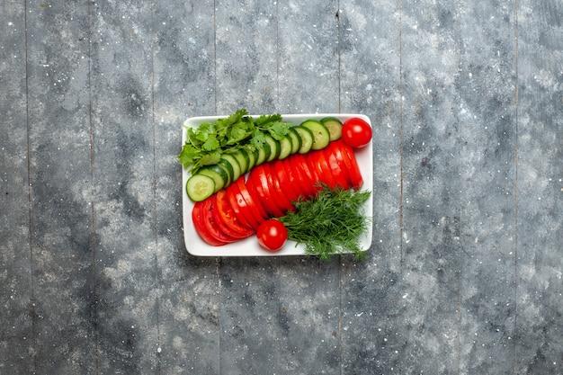 Vue de dessus salade de tomates fraîches en tranches élégamment conçues sur un espace rustique gris
