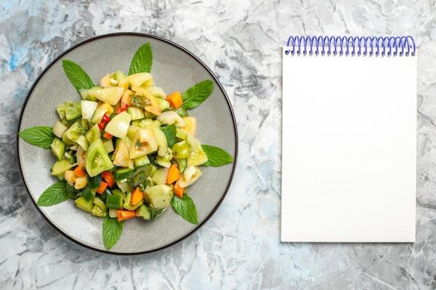 Vue de dessus de la salade de tomates vertes sur une assiette ovale un cahier sur fond gris