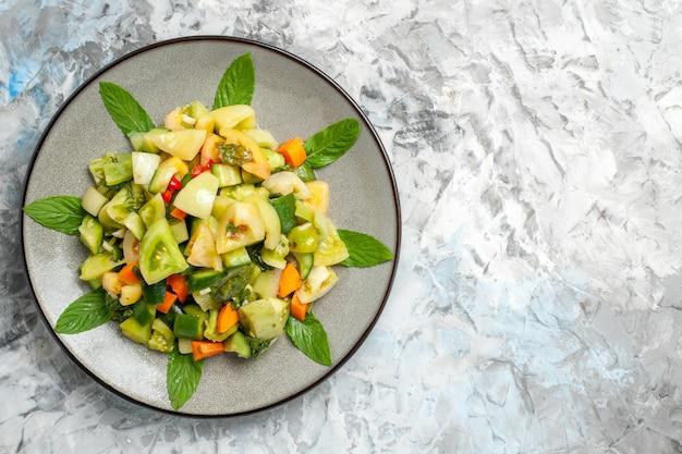 Vue de dessus de la salade de tomates vertes sur une assiette ovale sur fond sombre