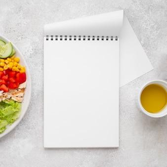 Vue de dessus salade végétarienne au poulet et huile avec bloc-notes vierge