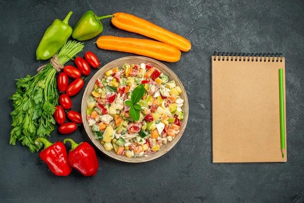 Vue de dessus de la salade végétarienne avec des légumes autour d'elle et bloc-notes sur le côté sur fond gris foncé