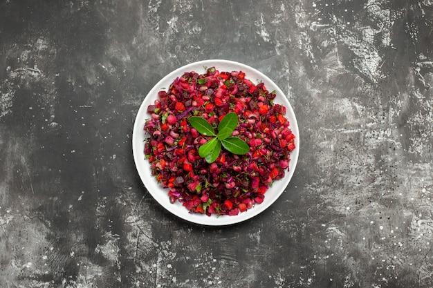 Vue de dessus salade avec vegtable rouge dans un plat blanc sur fond gris