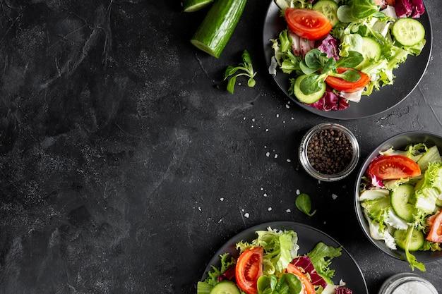 Vue de dessus des salades fraîches sur des assiettes sombres avec copie espace