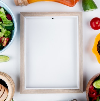 Vue de dessus des salades de légumes et des légumes comme la tomate concombre au beurre fondu au poivre noir et le cadre sur la surface blanche avec copie espace