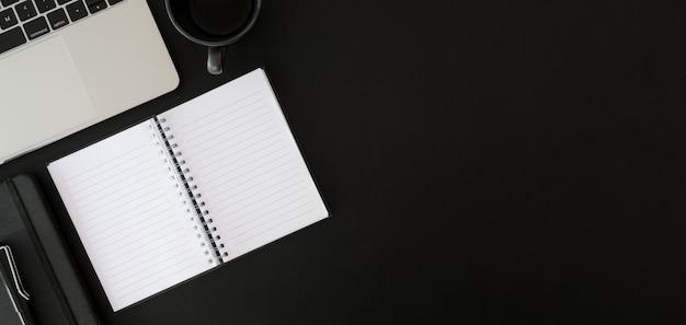 Vue de dessus de la salle de bureau moderne sombre avec cahier ouvert avec des fournitures de bureau et espace copie sur tableau noir