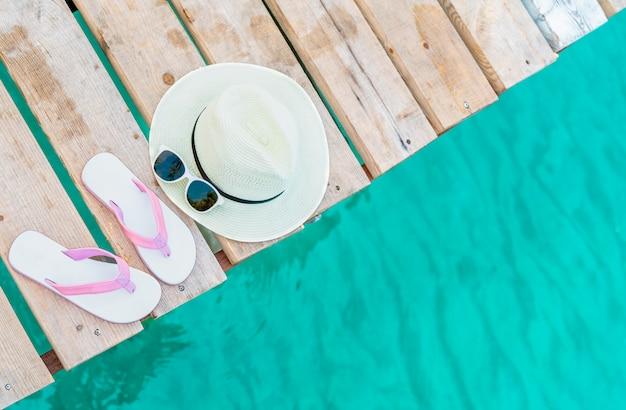 Vue de dessus de sandales rose-blanc, chapeau de paille et lunettes de soleil sur un pont en bois sur l'eau de mer vert émeraude