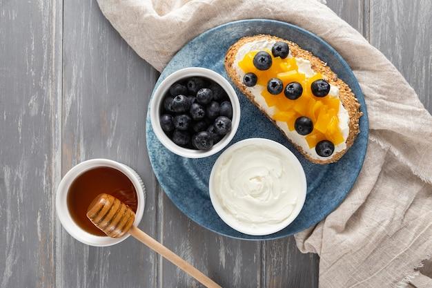 Vue de dessus sandwich avec fromage à la crème et fruits sur assiette avec du miel