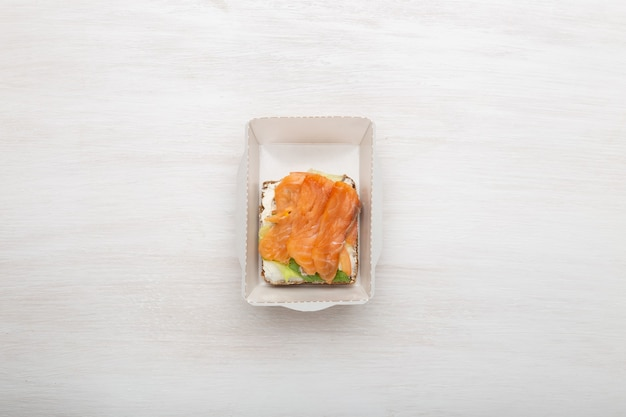 Vue de dessus sandwich avec fromage à pâte molle et poisson rouge se trouve dans la boîte à lunch à côté des légumes verts et des tomates sur un mur blanc avec espace de copie. concept d'une collation saine.