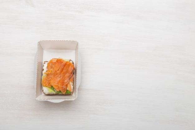 Vue de dessus sandwich avec fromage à pâte molle et poisson rouge se trouve dans la boîte à lunch à côté des verts et des tomates sur un fond blanc avec espace de copie. concept d'une collation saine.