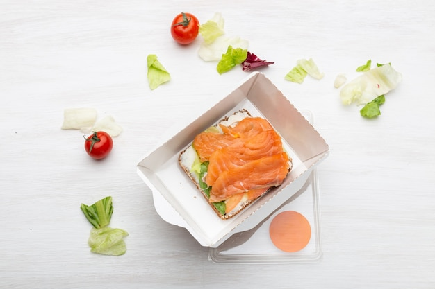 Vue de dessus sandwich avec fromage à pâte molle et poisson rouge se trouve dans la boîte à lunch à côté des verts