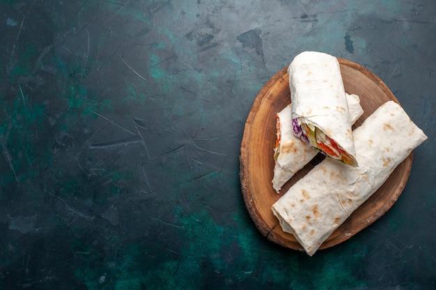 Vue de dessus sandwich à la viande un sandwich fait de viande grillée à la broche avec des légumes sur le bureau bleu foncé sandwich burger repas repas déjeuner viande photo
