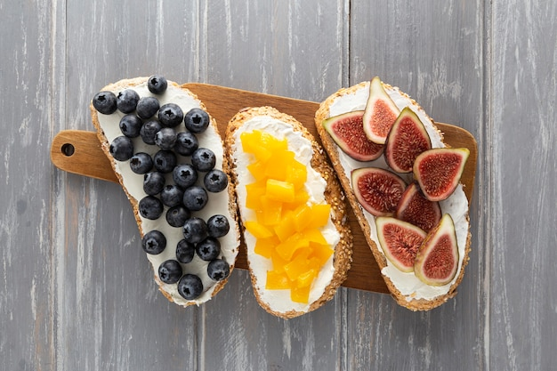 Vue de dessus des sandwichs avec du fromage à la crème et des fruits sur une planche à découper