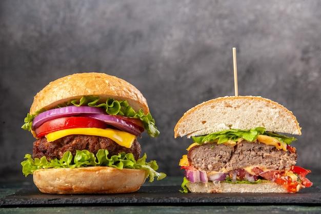 Vue de dessus des sandwichs savoureux entiers coupés sur un plateau noir sur une surface de couleur mélange sombre