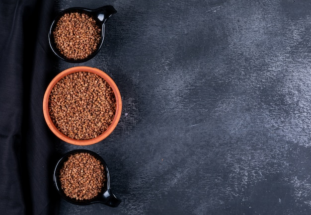 Vue de dessus de sarrasin dans un bol et des tasses noires avec un tissu noir sur fond sombre. espace horizontal pour le texte