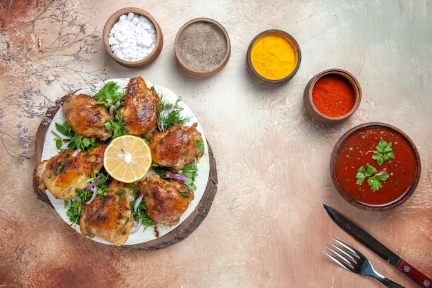 Vue de dessus de la sauce au poulet couteau fourchette poulet aux herbes de citron épices dans des bols