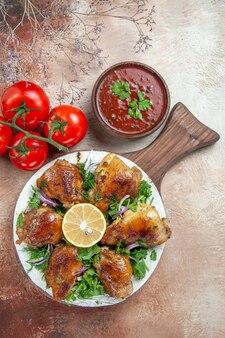 Vue de dessus de la sauce au poulet tomates avec pédicelles poulet aux herbes de citron sur la planche