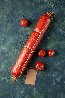 Vue de dessus des saucisses fraîches et savoureuses avec des tomates rouges sur fond sombre pain à la viande sandwich chignon couleur aliments pour animaux burger repas salade