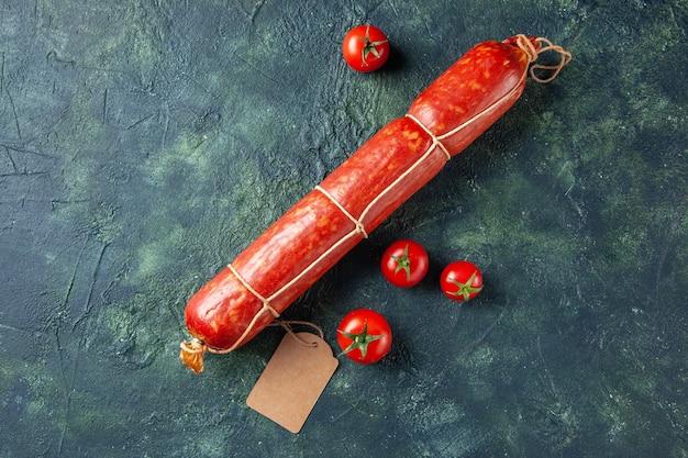 Vue de dessus des saucisses fraîches et savoureuses avec des tomates rouges sur fond sombre pain de viande sandwich repas chignon couleur hamburger d'aliments pour animaux