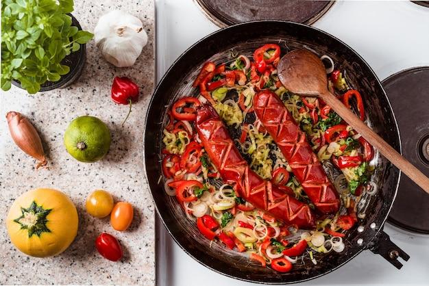 Vue de dessus des saucisses et mélange de légumes frits dans la poêle rustique