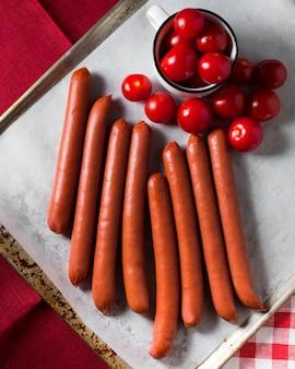 Vue de dessus des saucisses et des tomates cerises